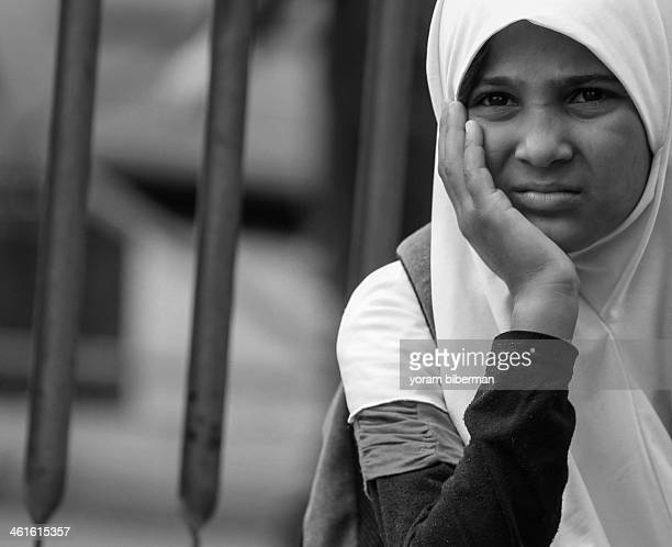 B&w portrait of a girl with a hijab, sitting, holding her palm on her face, thinking, looks a bit worried