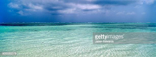 A tropical storm approaches the line of a reef on the horizon of calm turquoise seas.