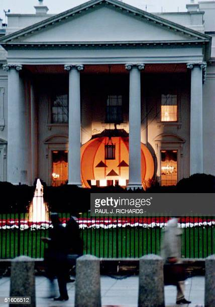 A 17 1/2 by 21foot jacko'lantern adorns the North Portico of the White House 26 October 1993 as pedestrians walk on Pennsylvania Ave The plywood...
