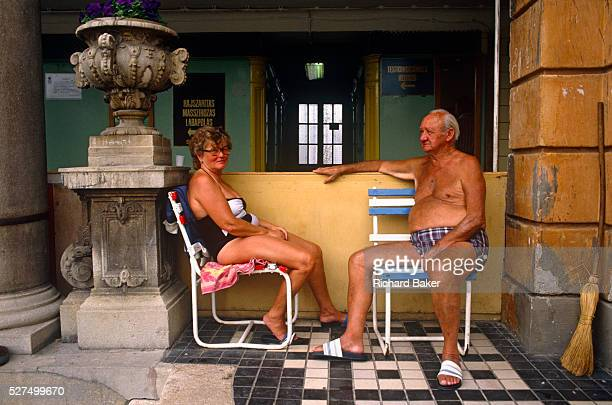 By a Neobaroque ornamental pillar and vase a Hungarian couple are seated on beach chairs not at the seaside but in Budapest's famous Sz��chenyi...