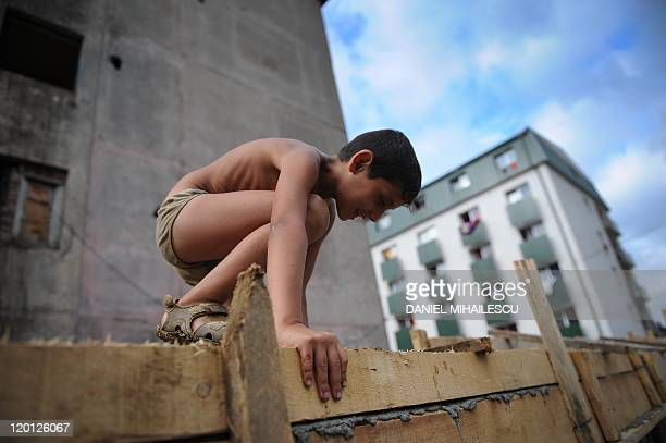BY by Anca Teodorescu A Roma child climbs on a concrete wall being built around a block of flats housing a majority of Roma families in Baia Mare on...