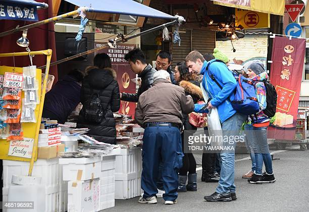 STORY by Anne BEADE This photo taken on March 3 2015 shows foreign tourists buying dried fish at a shop near the Tsukiji Fish Market in Tokyo Last...