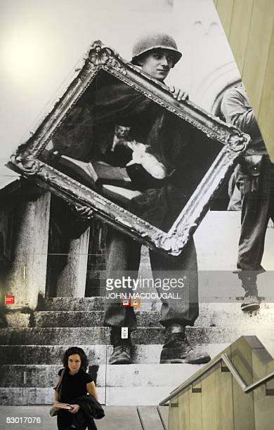STORY by ARNAUD BOUVIER FILES A visitor walks past a giant photograph featuring a US soldier holding up a painting looted by the Nazis from a Jewish...