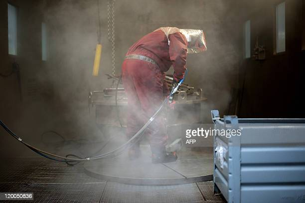 STORY by AURELIA END An employee of the Energiewerke Nord cleans dismantled parts of the Lubmin nuclear power plant on July 25 2011 at the Zentrale...