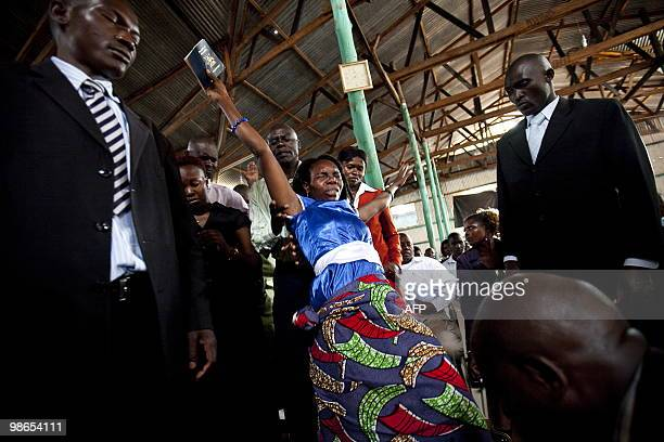 STORY by Ben SIMON An Ugandan woman exults in prayer as Ugandan Pentecostal pastor kneels during a service where he blessed his congregant�s...