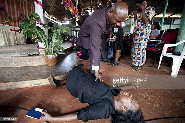 STORY by Ben SIMON Joshua Magezi a Ugandan Pentecostal pastor leans over a woman in trance and holding her passport during a ceremony where he...