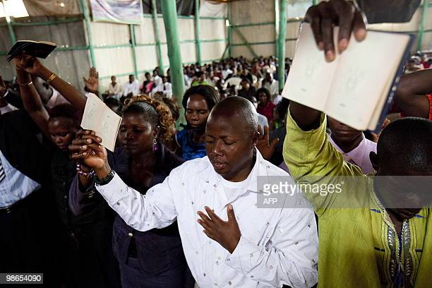STORY by Ben SIMON Martin Bwayo holds his passport as he and others pray during a ceremony at the Kibuli Miracle center during an Easter service...