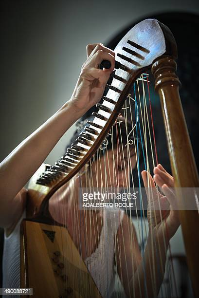 STORY by Carlos Batista Cuban musician Anaysa Nunez tunes her harp during a practice in Havana on May 12 2014 Due to the lack of special materials...