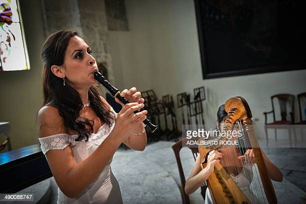 STORY by Carlos Batista Cuban musician Susana de la Cruz plays her recorder while Anaysa Nunez plays the harp during a practice in Havana on May 12...