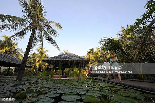 TOURISM by Charlie McDonaldGibson Foreign tourists walk past the lotus garden of a resort hotel in the seaside town Hua Hin on March 19 2008 As...