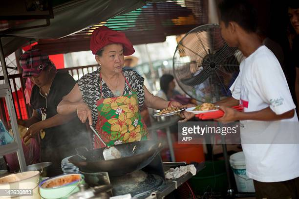 FEATURE by Dan Martin This photograph taken on February 23 2012 shows Soon Chuan Choo passing char kway teow to a customer in Georgetown the state of...