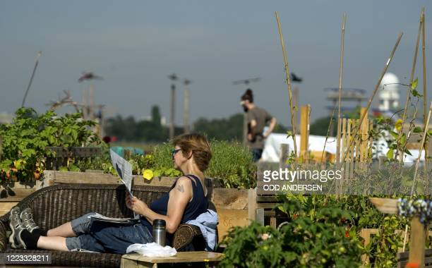 By DEBORAH COLE - A woman reads the paper seated on a bench among allotments at legendary Tempelhof Airport, the site of the Berlin Airlift and now...