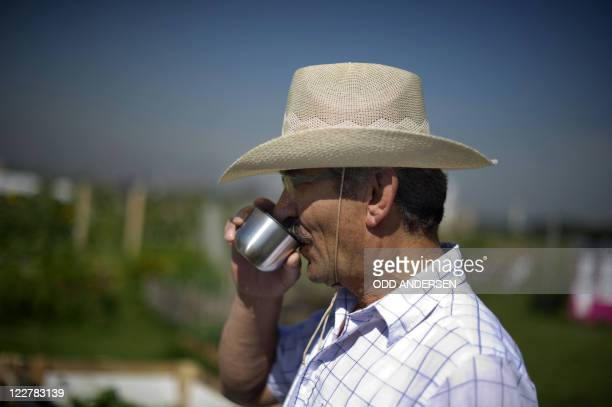 By DEBORAH COLE - Osman Dogan dons a cowboy hat as he sips coffee while tending to his plants on his allotment between the runways at legendary...