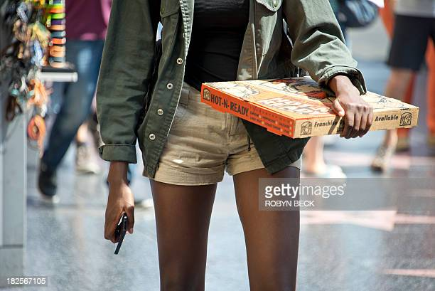 STORY by Fabienne Faur LifestylefoodUShealthteenagers A young woman carrying a pizza walks down Hollywood Boulevard in Hollywood California on...