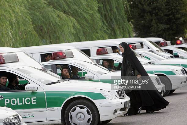 STORY by FARHAD POULADI An Iranian policewoman walks between police vehicles preparing to start a crackdown to enforce Islamic dress code in Tehran...