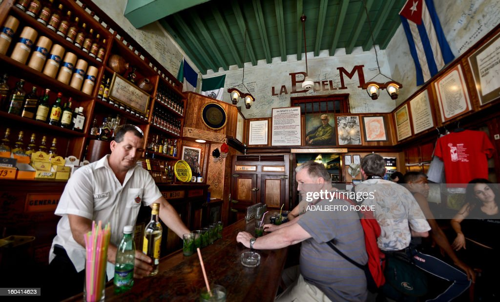 STORY by Francisco Jara A barman (L) makes mojitos for tourists at the famous Bodeguita del Medio bar in the Cuban capital, Havana, on April 23, 2012. April 26 will mark the 70th anniversary of La Bodeguita del Medio where US writer Ernest Hemingway drank 'mojitos'.