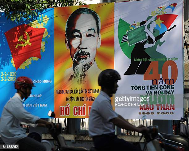 OFFENSIVE by Franck ZELLER Motorcyclists ride past billboards showing a large portrait of late president Ho Chi Minh and a poster marking the 40th...