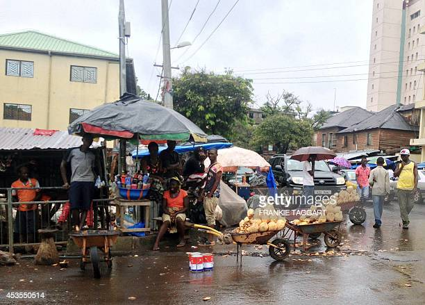 STORY by Frankie TAGGART Coconut sellers wait on a street corner in central Freetown on August 12 2014 The sprawling tropical city on the Atlantic...