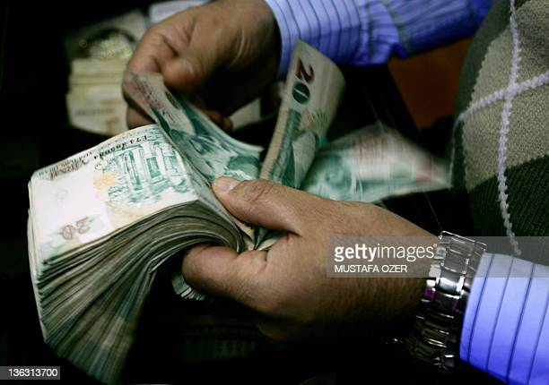 STORY by Fulya Ozerkan This file photo taken on April 30 2007 shows a man counting Turkish liras at a stockexchange office in Istanbul With the...