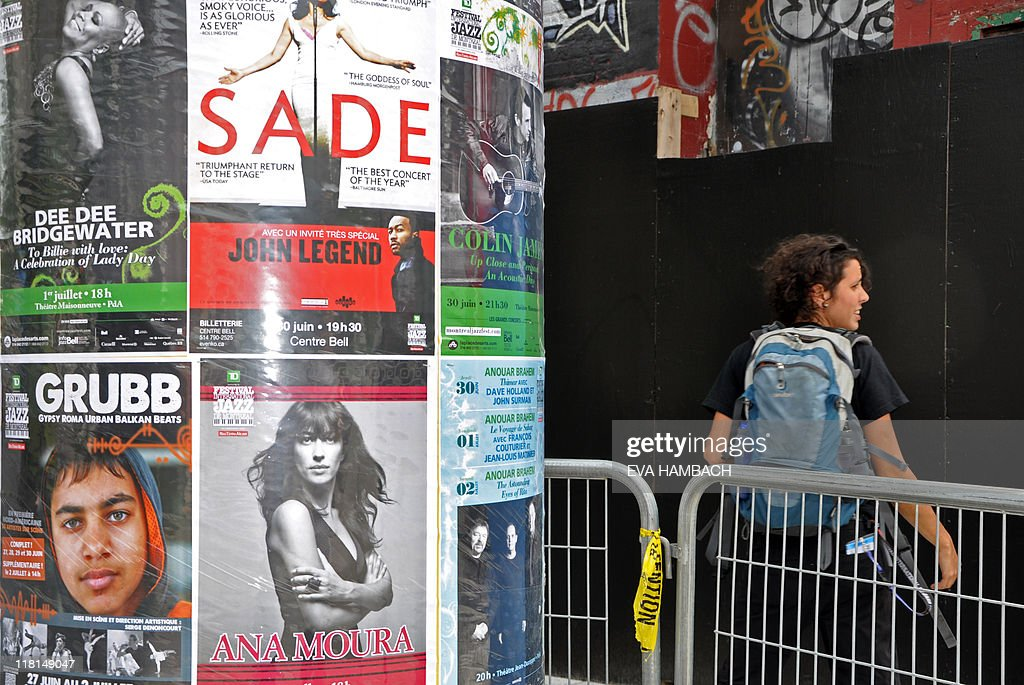 FESTIVAL by Guillaume LAVALLEE A woman walks by a poster featuring the band GRUBB - Gypsy Roma Urban Balkan Beats, performing at the Montreal International Jazz Festival on June 29, 2011 in Montreal, Quebec. The band made of 27 young gypsies from Serbia has seduced the public at the festival. AFP PHOTO/ Eva Hambach