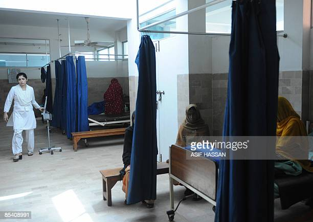 By Hasan Mansoor In this picture taken on March 3, 2009 a nurse passing by the beds of fistula patients at Koohi Goth hospital in the outskirts of...