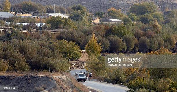 STORY 'PAKISTANAFGHANISTANQUAKEFARMTRADE' by Hasan Mansoor Pakistani commuters walk past an apple farm in Wam on November 2 2008 The sweeping valley...