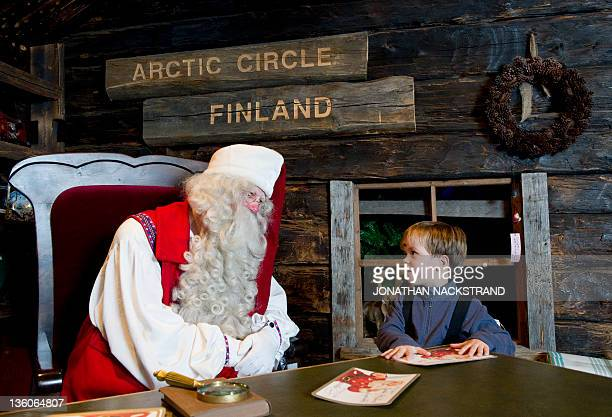 STORY by IGOR GEDILAGHINE FILES MORE IN IMAGE FORUM Santa Claus receives a wish list from a boy in his office in the Santa Park near Rovaniemi...