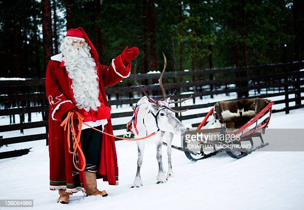 STORY by IGOR GEDILAGHINE FILES MORE IN IMAGE FORUM Santa Claus waves as he stands with a reindeer and sled outside Rovaniemi Finnish Lapland on...