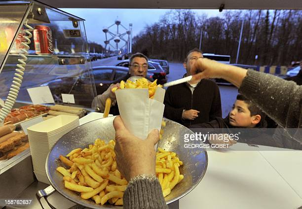 """By Jerome Rivet Josiane Devlaeminck serves Belgian fries to customers at the Atomium """"fritkot"""", the Flemish word for fries stand, in Brussels on..."""