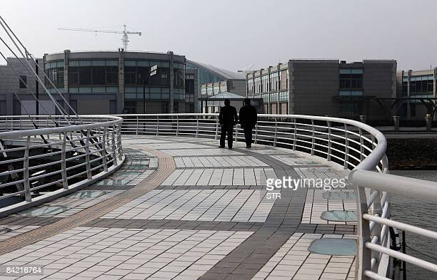 STORY 'CHINEECONOMIEURBANISME' by Julie Desne Two residents walk on the pedestrian bridge leading to the near empty shop lots in Lingang a 300...