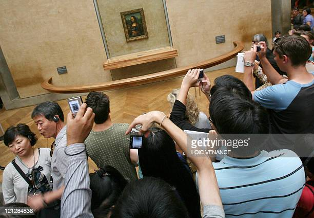 STORY by KERSTIN LOEFFLER FILES People take pictures of the Joconde painting by Italian artist Leonard de Vinci as they visit the Louvre museum on...