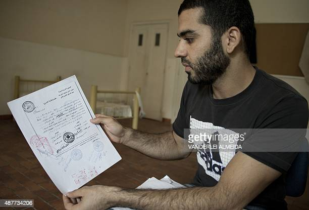 STORY by Laura Bonilla Syrian refugee Khaled Fares shows his dental prosthetic record during an interview with AFP at an accommodation he was...