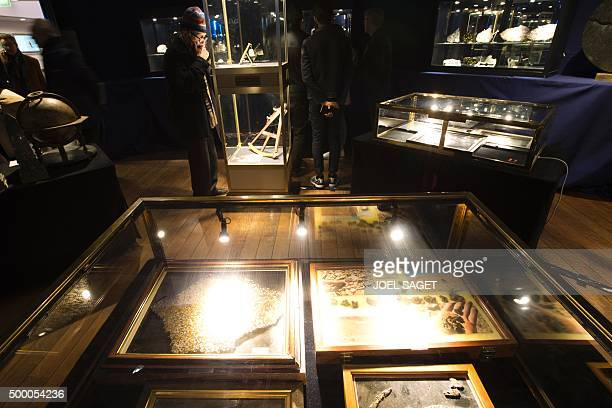 STORY by Laurence COUSTAL People look at meteorite fragments part of Pierre Delpuech collection displayed ahead of the Hotel Drouot's auction in...
