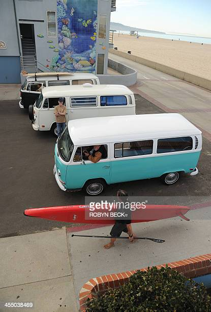 STORY by Leila MACOR LifestyleUStransportautosurf A paddleboarder walks past three Volkswagen Kombis in Hermosa Beach California on November 27 2013...
