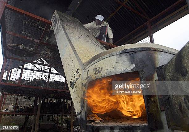 STORY by LUCIE PEYTERMANN FILES Picture made 11 August 2007 shows a slum resident feeding garbage into an improvised garbage incinerator at Africa's...