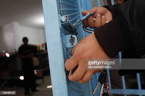 STORY by MAI YAGHI A Palestinian Hamas prison guard closes the gate of a cell in one of Gaza City's jails on December 9 2010 where drug addicts and...
