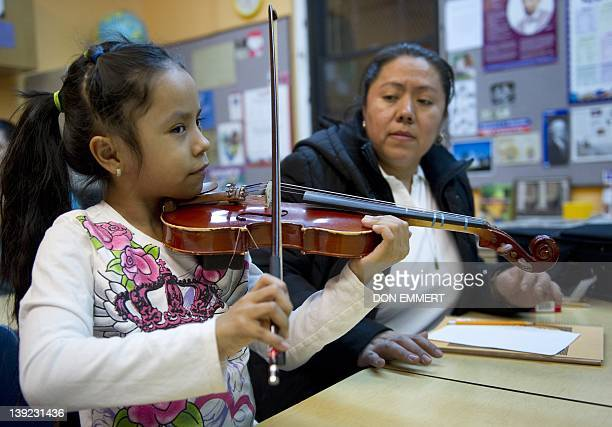 IMMIGRATION by Mariano Rolando A young girl plays the violin with some help from her mother during violin class at the Mariachi Academy February 6...
