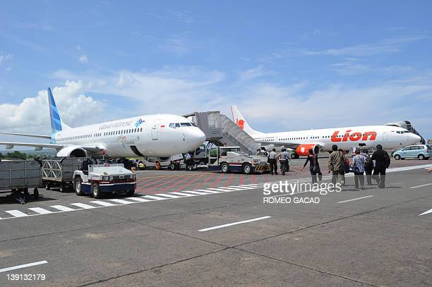 INDONESIA FOCUS by Martin Abbugao In this photograph taken on November 22 passengers board a Garuda plane while a nearby Lion Air aircraft sits...