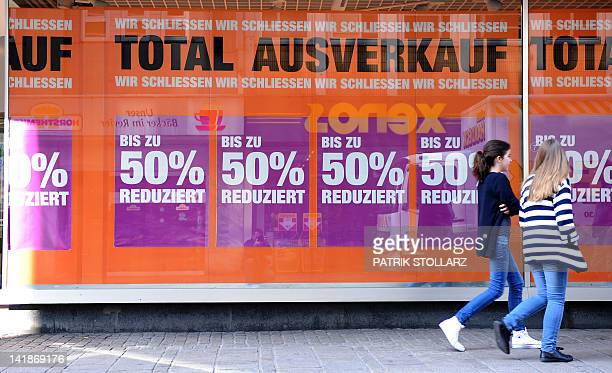 STORY by MATHILDE RICHTER Picture taken on March 22 2012 shows two girls walking past a shop offering sales as it is closing down on the main road in...