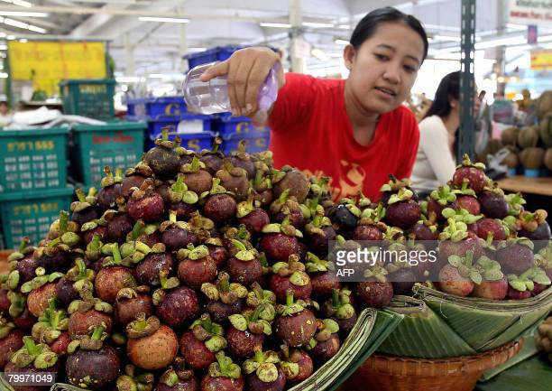 STORY THAILANDUSTRADEFRUITFARM by Nareerat Wiriyapong A Thai fruit vendor sprays water on mangosteens at market in Bangkok on October 21 2007 Thai...