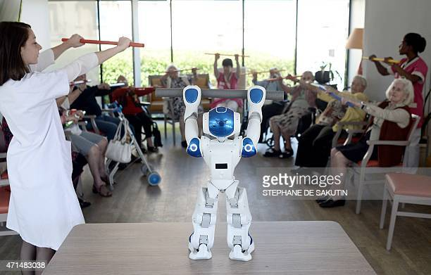 STORY by Nathalie ALONSO Elderly people look at a health worker and Nao a humanoid robot of the Institute for Intelligent Systems and Robotics at a...