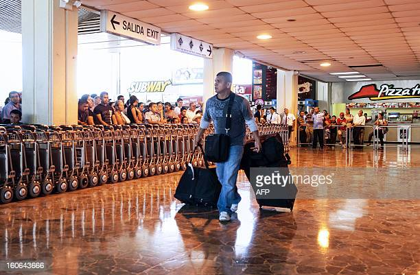 STORY by Oscar Batres A man carries his luggage at Comalapa International Airport 44 km south of San Salvador as people wait for their loved ones...
