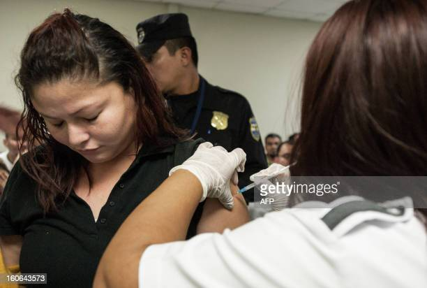 STORY by Oscar Batres A Salvadoran deported from the US is vaccinated at the immigration office in Comalapa International Airport 44 km south of San...