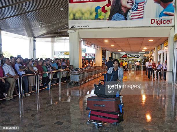 STORY by Oscar Batres A woman carries her luggage at Comalapa International Airport 44 km south of San Salvador as people wait for their loved ones...
