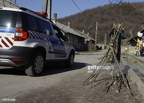 STORY by PETER A police car passes a local gypsy who caries some wood in Ozd northern Hungary on March 14 a few weeks ahead of the general elections...