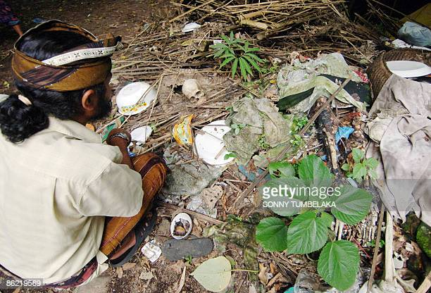 STORY INDONESIABALICULTUREDEATH by Presi Mandari A Balinese man sits next to a grave near a banyan tree at Trunyan village in Bangli on the resort...