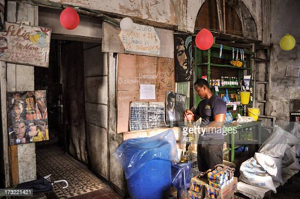 STORY by Rigoberto Diaz A shopkeeper fills bottle with cooking oil at a store where people can use their libreta a ration card which since 1963 has...