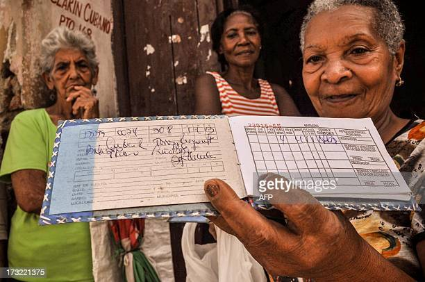 STORY by Rigoberto Diaz An elderly woman shows a libreta a ration card which since 1963 has allowed Cubans to buy basic food supplies at cheap and...