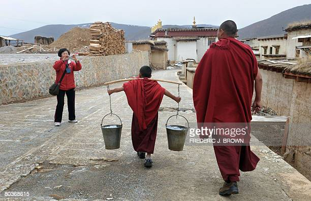 By Robert Saiget A Han Chinese tourist snaps pictures of a young Tibetan Buddhist monk carrying a heavy load of water at the Ganden Sumtseling...