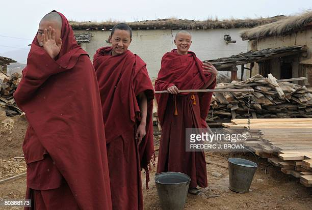 By Robert Saiget Tibetan Buddhist monks at the Ganden Sumtseling Monastery in Shangrila gesture while collecting water for evening chores on March...